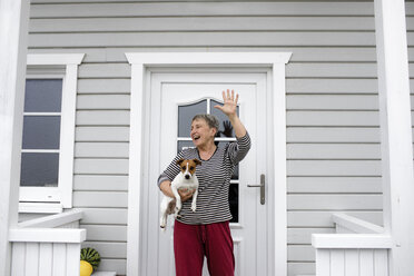 Happy senior woman on porch with her dog raising her hand - KMKF00968