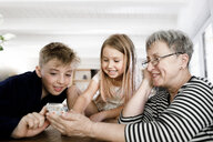 Happy grandmother and grandchildren using  cell phone at home - KMKF00971