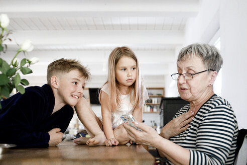 Grandmother and grandchildren using  cell phone at home - KMKF00974