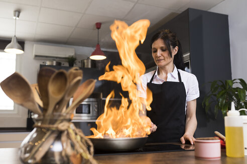 Woman cooking in kitchen flambing food in a pan - ABZF02371