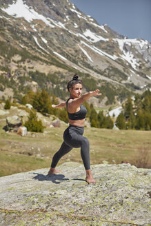 Young woman doing yoga  standing on rock in nature, warrior pose - JPF00397