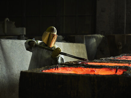 Industry, worker checking liquid copper in casting moulds with pliers - CVF01216