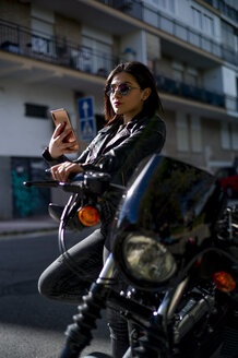Portrait of young woman leaning against motorbike looking at smartphone - OCMF00457