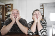 Portrait of adult son with senior mother sitting at table at home with head in hands - KMKF00979