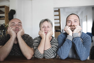 Portrait of adult sons with senior mother sitting at table at home with head in hands - KMKF00982
