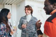 Friends talking at party in loft office - CUF51287