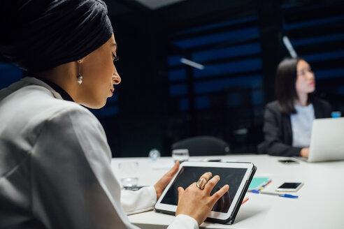 Businesswoman using digital tablet during office presentation, over shoulder view - CUF51326