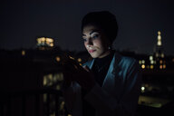Young businesswoman looking smartphone on office balcony at night - CUF51332