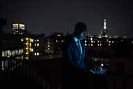 Young businessman typing on laptop on office balcony at night - CUF51335