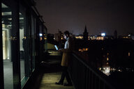 Mid adult businessman looking at laptop on office balcony at night - CUF51341