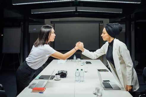 Businesswomen shaking hands over conference table - CUF51359