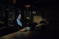 Young businesswoman in office at night typing on laptop - CUF51362