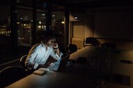 Tired young businessman in office at night typing on laptop - CUF51368