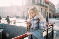 Young woman looking at smartphone by underground station, Milan, Italy - CUF51371