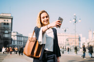 Young female tourist taking smartphone selfie in city square, Milan, Italy - CUF51377