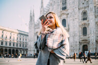 Young female tourist talking at smartphone by Milan Cathedral, Milan, Italy - CUF51380