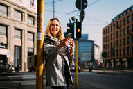 Young woman with smartphone laughing at tram station, Milan, Italy - CUF51383