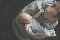 Top view of father holding his sleeping newborn baby daughter - IHF00011