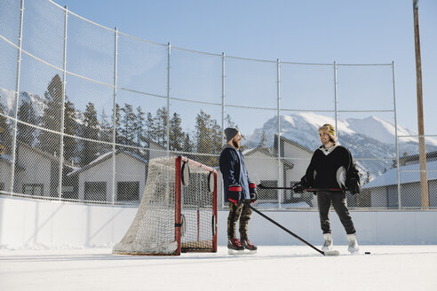 Men talking, playing outdoor ice hockey - HEROF36209