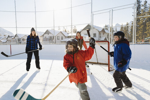 Family playing outdoor ice hockey - HEROF36227