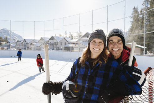 Portrait happy couple playing outdoor ice hockey - HEROF36236