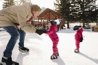 Father and toddler daughter ice skating on frozen pond - HEROF36245