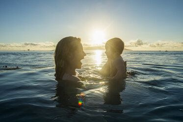 French Polynesia, Tahiti, Papeete, woman playing with her little baby in an infinity pool at sunset - RUNF02059