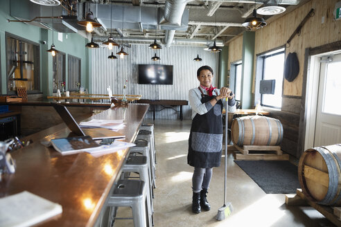 Portrait confident female business owner sweeping brewhouse - HEROF36304