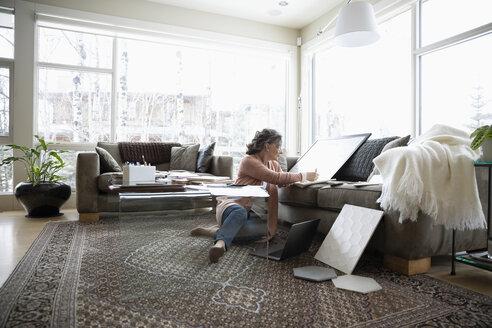 Senior female interior designer working in living room - HEROF36322