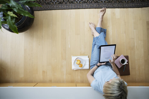 View from above barefoot woman working from home, using digital tablet on floor - HEROF36364