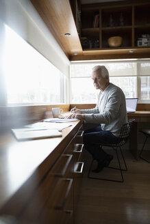 Senior man working in home office, reviewing paperwork - HEROF36379