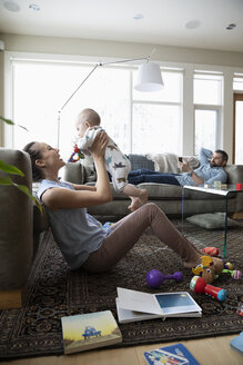 Happy mother playing with baby son in living room - HEROF36415
