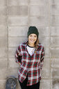 Portrait smiling young female skateboarder leaning against concrete wall - HEROF36445
