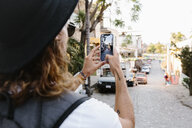 Young male tourist using camera phone on street, Mexico - HEROF36490