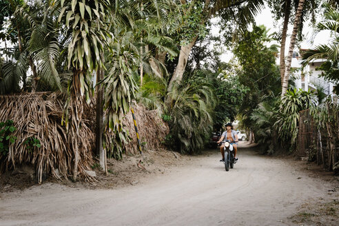 Young man riding motorcycle on tropical dirt road, Mexico - HEROF36493