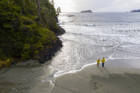 Couple on remote, rugged ocean beach, British Columbia, Canada - HEROF36514