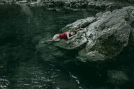 Caucasian woman laying on rocks in pool of water - BLEF03256