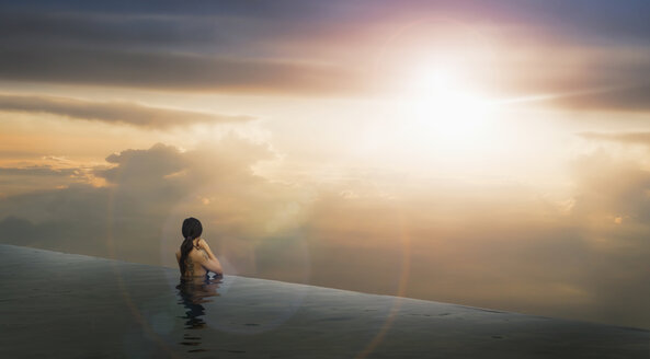 Chinese woman in infinity pool admiring sunset - BLEF03274