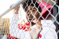 Curious Black man leaning on chain-link fence - BLEF03286