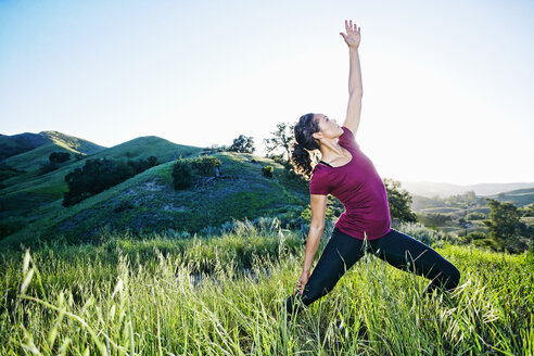 Mixed Race woman practicing yoga on hill - BLEF03310