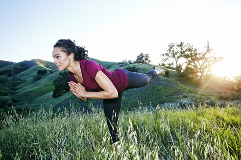 Mixed Race woman practicing yoga on hill - BLEF03316