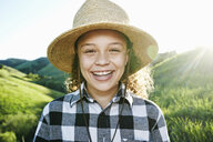 Smiling girl wearing hat on sunny hill - BLEF03328