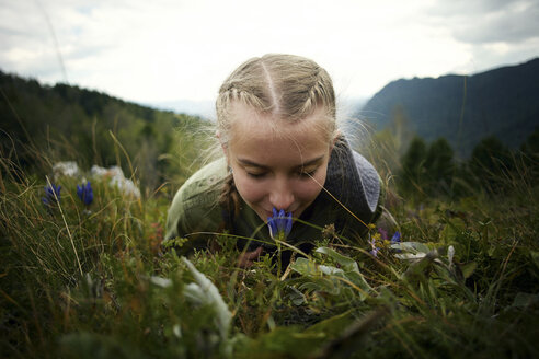 Caucasian girl smelling wildflower laying in grass on hill - BLEF03376