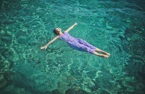 Caucasian woman wearing dress floating in water - BLEF03391
