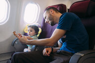 Father playing with his little daughter on airplane - GEMF02948