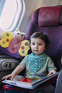 Portrait of toddler girl sitting on airplane - GEMF02951