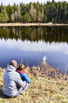 France, Pyrenees, back view of father and little daughter sitting in front a lake looking at view - GEMF02960