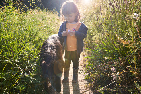 Toddler girl walking with dog in nature - GEMF02969