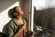 Young woman at the window enjoying the sunshine - GUSF01963