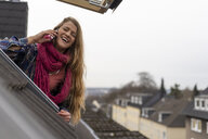 Happy young woman on cell phone leaning out of roof window - GUSF01966